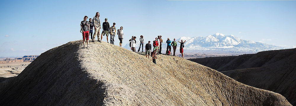 Students from the University of Colorado course in geomorphology pose for a group portrait in the mancos shale badlands near Factory Butte, Utah. The Henry Mountains are visible in the background.