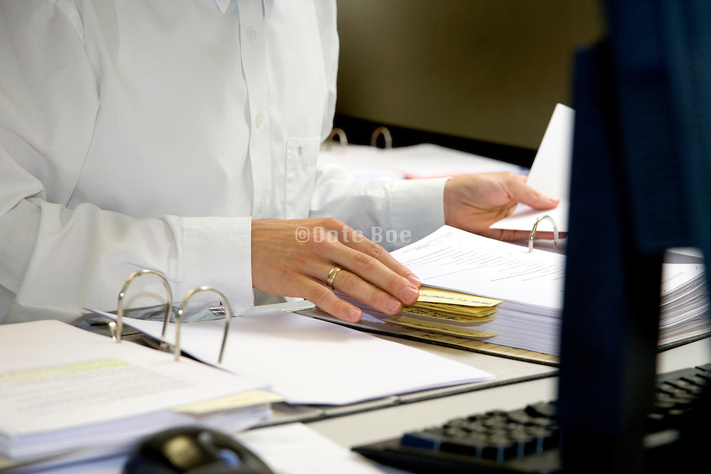 office worker looking information up in a traditional binder