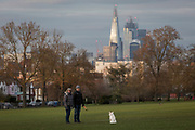 With the Shard and other City buildings in the background, two dog owners wait for their pet to come, in Lambeth's Ruskin Park, on 11th February 2019, in London, England.