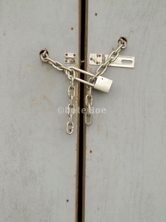 Close up of a wooden gate locked with a chain and padlock