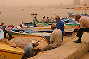 Repairing small wooden boats on the beach of the port of Alexandria, Egypt during a sandstorm. The yellow-orange light is from the sand in the sky filtering the sunlight.