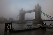 Thick fog over London at Tower Bridge making a peaceful yet eerie atmosphere as structures appear and disappear over the River Thames.