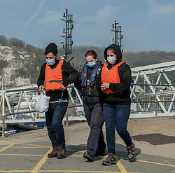 © Licensed to London News Pictures. 24/03/2021. Dover, UK. Two people being escorted form a boat at Dover, Kent by Border Force officers. Home Secretary Priti Patel has pledged an overhaul of asylum seeker rules, with refugees having their claim assessed based on how they arrive in the UK. Photo credit: Stuart Brock/LNP