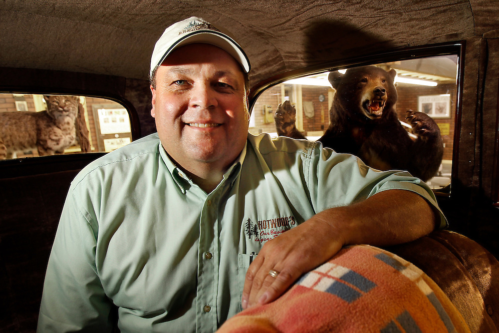Kevin Houtwed, collector, in his 1934 Ford with a blanket his mother had with her 1934 Ford as well as two mounted animals at Hotwood's in Grand Island. (Independent/Matt Dixon)