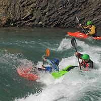 Kayakers play in waves on the Kananaskis River in the Canadian Rockies near Calgary, Alberta.