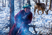 A Tsaatan man sitting in front of a fire up in the mountains watching over his grazing reindeer herd (Rangifer tarandus) in order to protect it from wolves, Khovsgol Province, Mongolia