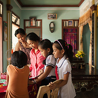 Looking at a book together in a home in in Thủy Phư commune. Village life includes much visiting of family and neighbors during the long hot afternoons.