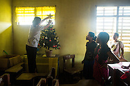 Seventh grade students watch as their teacher places a star atop their classroom Christmas tree at storm-damaged Candalaria National High School, which was being used as a medical clinic site in the wake of Typhoon Haiyan, in the village of Roxas Ocho, Philippines.