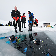 Richard Morris and Heloise Chenelot prepare to go beneath the surface of the ice of the Arctic Ocean.