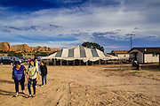 "12 JULY 2012 - FT DEFIANCE, AZ:  A family walks to the youth worship service, past the main tent, at the 23rd annual Navajo Nation Camp Meeting in Ft. Defiance, north of Window Rock, AZ, on the Navajo reservation. Preachers from across the Navajo Nation, and the western US, come to Navajo Nation Camp Meeting to preach an evangelical form of Christianity. Evangelical Christians make up a growing part of the reservation - there are now more than a hundred camp meetings and tent revivals on the reservation every year. The camp meeting in Ft. Defiance draws nearly 200 people each night of its six day run. Many of the attendees convert to evangelical Christianity from traditional Navajo beliefs, Catholicism or Mormonism. ""Camp meetings"" are a form of Protestant Christian religious services originating in Britain and once common in rural parts of the United States. People would travel a great distance to a particular site to camp out, listen to itinerant preachers, and pray. This suited the rural life, before cars and highways were common, because rural areas often lacked traditional churches.    PHOTO BY JACK KURTZ"