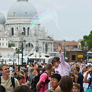 VENICE, ITALY - JULY 28:  A little girl bursts  a large soap bubble amoung the very crowded St Marks Square --------------------<br /> FOR LARGER RESOLUTION OR TO LICENCE THIS PICTURE: please contact us via e-mail at sales@xianpix.com or call our offices in Milan at (+39) 02 400 47313 or London   +44 (0)207 1939846 for prices and terms of copyright. First Use Only ,Editorial Use Only, All repros payable, No Archiving.© MARCO SECCHI