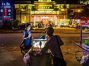 "13 FEBRUARY 2019 - SIHANOUKVILLE, CAMBODIA:  A Cambodian worker at the MGM Casino buys food from a street vendor after her shift. The MGM is a Chinese owned casino. There are about 80 Chinese casinos and resort hotels open in Sihanoukville and dozens more under construction. The casinos are changing the city, once a sleepy port on Southeast Asia's ""backpacker trail"" into a booming city. The change is coming with a cost though. Many Cambodian residents of Sihanoukville  have lost their homes to make way for the casinos and the jobs are going to Chinese workers, brought in to build casinos and work in the casinos.      PHOTO BY JACK KURTZ"