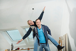 Man giving his female partner a piggyback while renovation