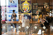 Shanghai coffee shop with advertising reflected and people on mobile telephones