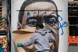 "© Licensed to London News Pictures . 22/07/2020 . Manchester , UK . A mural to George Floyd in the Northern Quarter of Manchester City Centre is repainted by the artist after it was sprayed with racist graffiti . "" Nigger "" was sprayed across the face of the artwork by Manchester artist AKSE overnight . Photo credit : Joel Goodman/LNP"