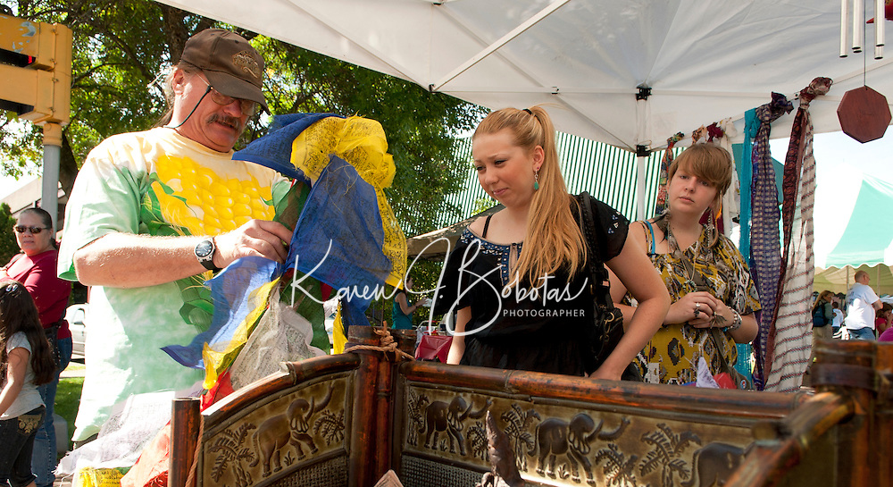 Michael Folsom shows a Nepali prayer flag to Rachel King and Katelyn VanderClute during the 10th annual Multicultural Market Day festivities in downtown Laconia Saturday.  (Karen Bobotas/for the Laconia Daily Sun)Multicultural Market Day in Laconia.  (Karen Bobotas/for the Laconia Daily Sun)
