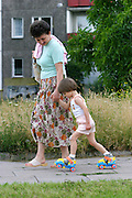 Mother and daughter learning to rollerskate. Warsaw, Poland.