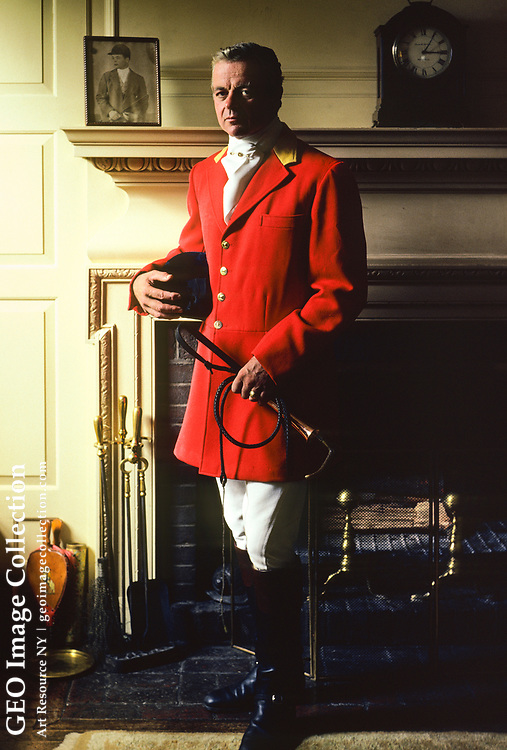 Neil Rice Ayer, Master of Foxhounds of the Myopia Hunt, in the parlor of his mother's house at Ledyard Farm, Wenham, Massachusetts. Mr. Ayer is wearing the brilliant scarlet Red Hunting Coat known as Hunting Pinks. President of the United States Combined Training Association or USCTA from 1971 to 1982, he is a legendary sportsman in the development of Eventing in America and is credited with the sports' success in the 1970s and 1980s. Mr. Ayer developed Ledyard Farm into a world-class cross-country course. He broke his neck playing polo in 1971 but continued to ride and supported equestrian safety and education.