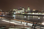 Night scene looking over to the City of London on a cold snowy winter evening. Snow comes down heavily in the heaviest early winter weather in many years, obscuring the skyline.