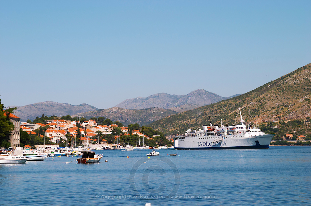 Pleasure boats moored on buoys and along the key, villas along the coast. A big cruise ship Jadrolinja arriving in the harbour. Mountains mountain tops in the background. Luka Gruz harbour. Dubrovnik, new city. Dalmatian Coast, Croatia, Europe.