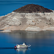 """The Desert Princess, a three-level paddle-wheeler, passes Rock Island, November 17, 2014, while leaving HemenwayHarbor on it mid-day sightseeing cruse.  A high-water mark or """"bathtub ring"""" is visible on the shoreline; Lake Mead is down over 145 vertical feet."""