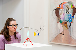 "© Licensed to London News Pictures. 30/09/2016. London, UK.   (L) ""Two Legs and a Belly"" by Alexander Calder (est. GBP300-500k) is viewed by a staff member and (R) ""The Pilot"" by George Condo (est. GBP375-475k) at the preview of Sotheby's London upcoming Contemporary Art Auctions.  Photo credit : Stephen Chung/LNP"