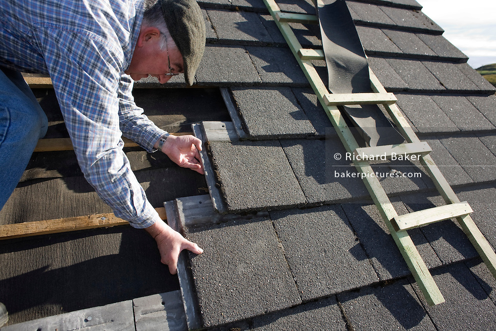 Active retired pensioner carefully bends to aligns new tiles on roof of his cottage before winter arrives on the Isle of Skye