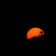 Heather Goodrich riding through and under the autumn sunset.