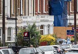 © Licensed to London News Pictures. 18/08/2018. Catford, UK. Investigators in protective suits (R) stand outside a property where a man in his 50's has been stabbed to death in Catford, south London. Police were called at 4am, the victim was pronounced dead at the scene at 5.28am. No arrests have been made. Photo credit: Peter Macdiarmid/LNP