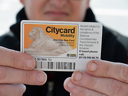 Man with disability displays his concessionary bus pass.