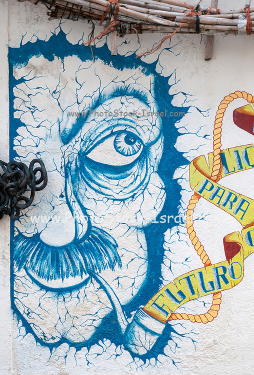 Colourful elaborate graffiti of a man's face smoking a pipe. Photographed in Nazare, Portugal