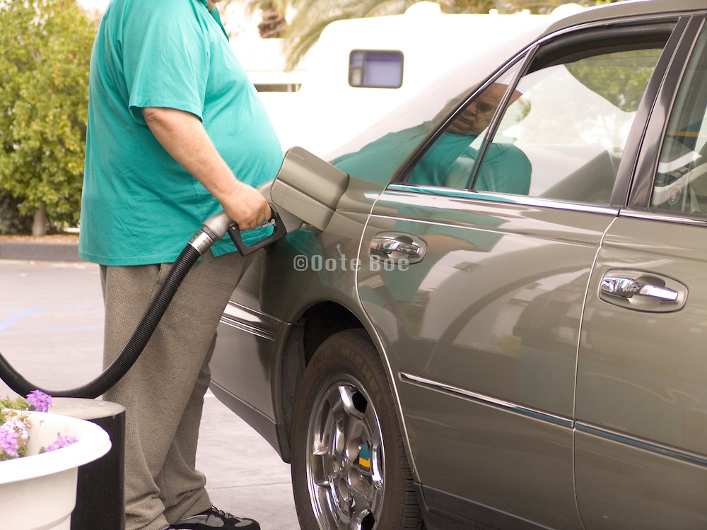 close up of a obese man filling his gas tank
