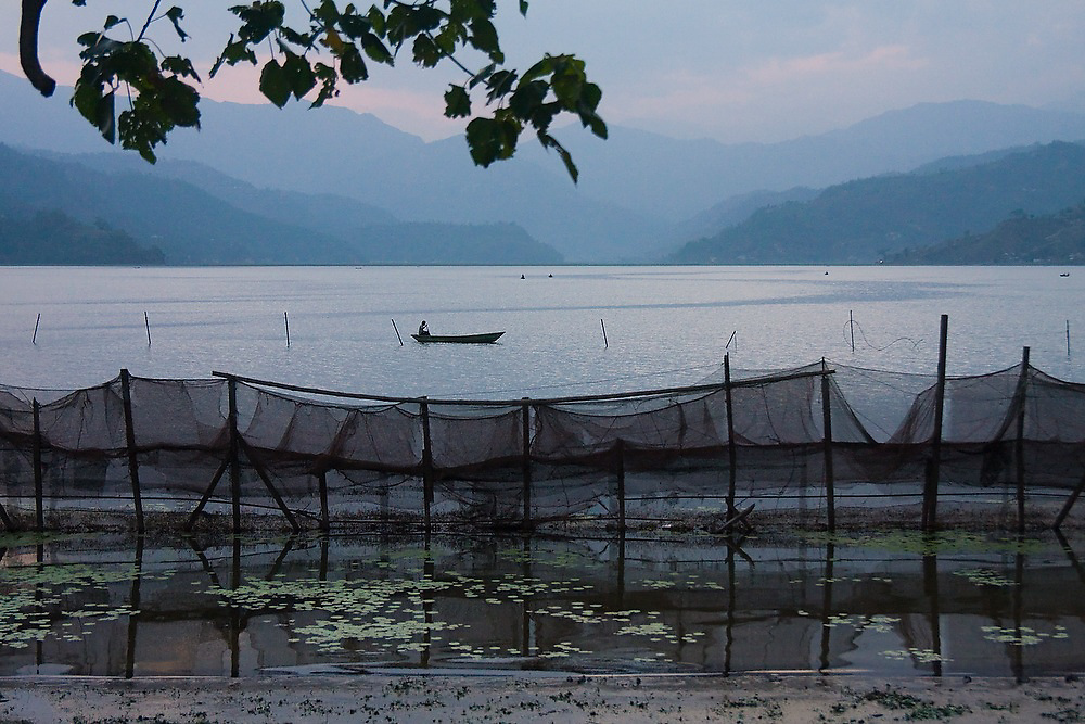 A villager in a small wooden boat floats alone on the still surface of Lake Phewa Tal in Pokhara, Nepal. Fish farms are visible in the foreground.