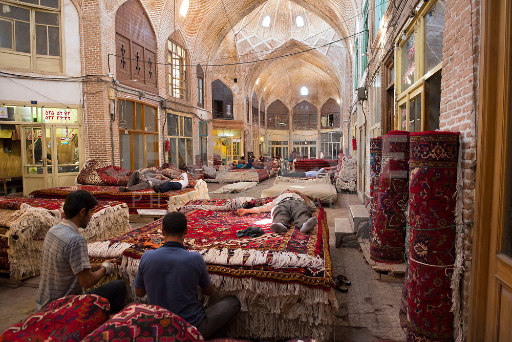 Iran, Tabriz, 23.08.2016: Schlafende Teppichhändler am Nachmittag auf dem Basar in Tabriz, Männer bei der Restauration gebrauchter Perserteppiche. Provinz Ost-Aserbaidschan, Nordwest-Iran.