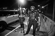 Police in riot geaer during a George Floyd solidarity protest  In New Orleans on June 3, thousands of people went on the Crescent City Connection to try to cross the bridge only to be teargassed by the police.