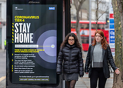 © Licensed to London News Pictures. 29/12/2020. London, UK. Members of the public walk past a Covid-19 information display in Fulham, South West London as NHS chiefs say that health workers are back in the eye of the storm as cases soar throughout London and the UK. Ministers are expected to roll out vaccinations to start from the 4 January 2021 as they mull over putting parts of the country into tier 5 restrictions to slow the spread of the virus. Last week Health Secretary Matt Hancock announced another new Covid-19 mutation has been discovered in the UK as Downing Street ordered many more areas of England to go into Tier 4 lockdown with tougher new Covid-19 restrictions for many as the mutated strains continue to spread throughout the UK. Photo credit: Alex Lentati/LNP