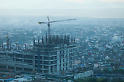 Early morning photo showing the dense smog in Manila with a crane and building under construction in the foreground.