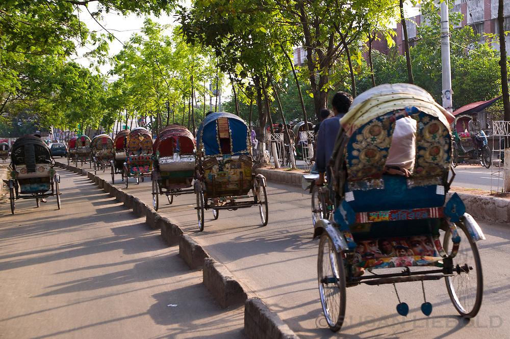 Rickshaws driving in a line on the streets of Dhaka, Bangladesh. Jalal's rickshaw is the one at the end.
