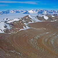A rock-strewn glacier flows out of the Wolthat Mountains, Queen Maud Land, Antarctica.