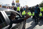 A man gestures to police as protesters block traffic, climate change protest group Extinction Rebellion stage a protest at London City Airport during day four of two weeks of planned demonstrations on 10th October, 2019 in London, Untited Kingdom. Extinction Rebellion is demanding that governments drastically cut carbon emissions.