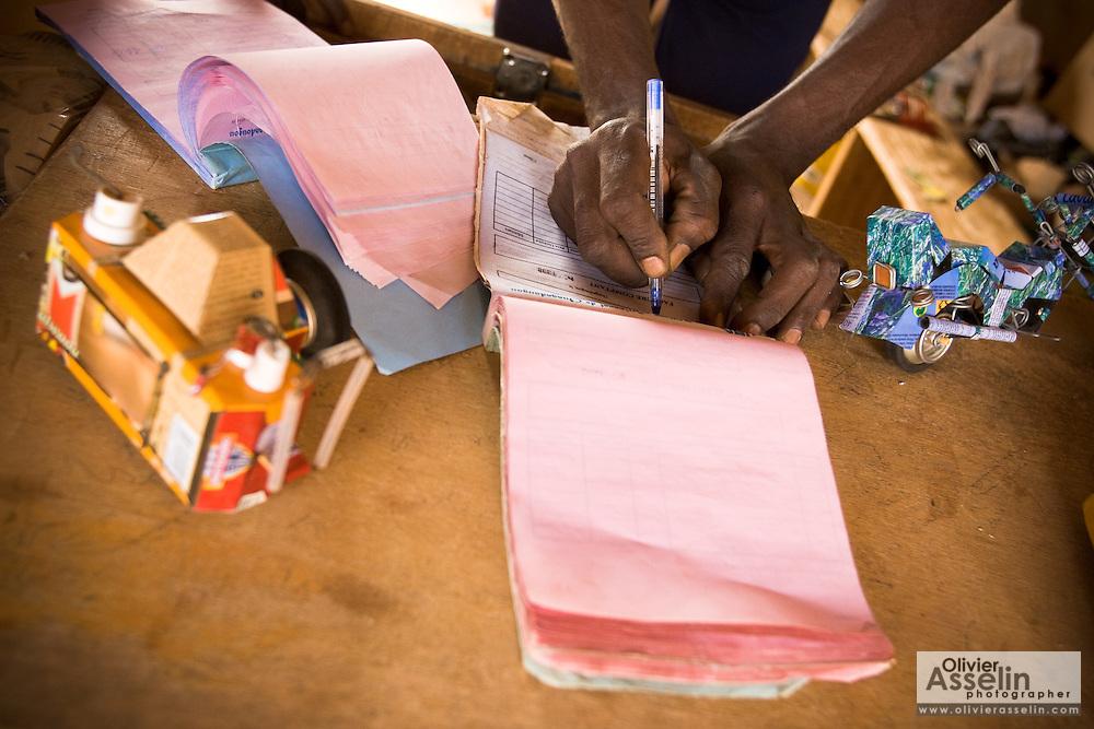 A man fills an invoice after making a sale at the Village Artisanal de Ouagadougou, a cooperative that employs dozens of artisans who work in different mediums, in Ouagadougou, Burkina Faso, on Monday November 3, 2008.