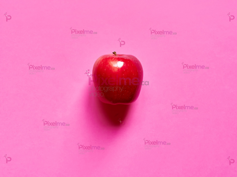 Above view of a red apple isolated in a fucsia background in studio top view