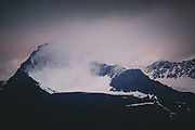 Holding Snow | Mountain peak with snow, clouds and heavy wind, Norway