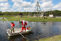 December 20, 2017 - Loxahatchee, Florida, U.S. - Santa waves to the crowd as he prepares to deliver presents to Lion Country Safari's 16 chimpanzees during the 33rd annual Christmas with the Chimps in Loxahatchee, Florida on December 20, 2017.  This years Christmas with the Chimps was dedicated to Little Mama the 79-year-old chimpanzee who passed away in November. The park's chimpanzees received gifts including edible treats, stuffed animals, clothes and enrichment-themed activities. ''Chimpanzees are extremely intelligent. They recognize that the gathering crowd of guests signals that Santa is on his way. They also read human emotions very well, and react to the excitement and anticipation of our guests. The whole day is really very enriching for them,'' says Primate Curator Tina Cloutier Barbour. Over the 33 years, it has developed into a community event and this year featured the Cypress Trails Elementary School's ''Singing Lions'' chorus. This is the only event where guests are permitted out of their vehicles. (Credit Image: © Allen Eyestone/The Palm Beach Post via ZUMA Wire)