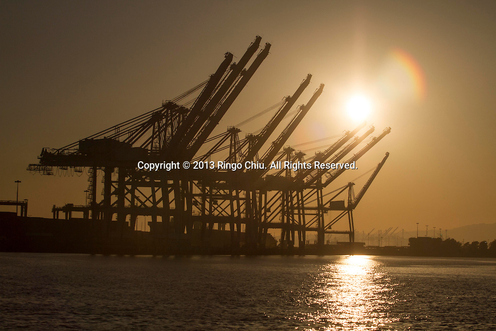 The dark silhouette of the machinery and cranes of the container terminal stand against the backdrop of a sunset evening sky at the Long Beach Port , California on March 12, 2013. (Photo by Ringo Chiu/PHOTOFORMULA.com).