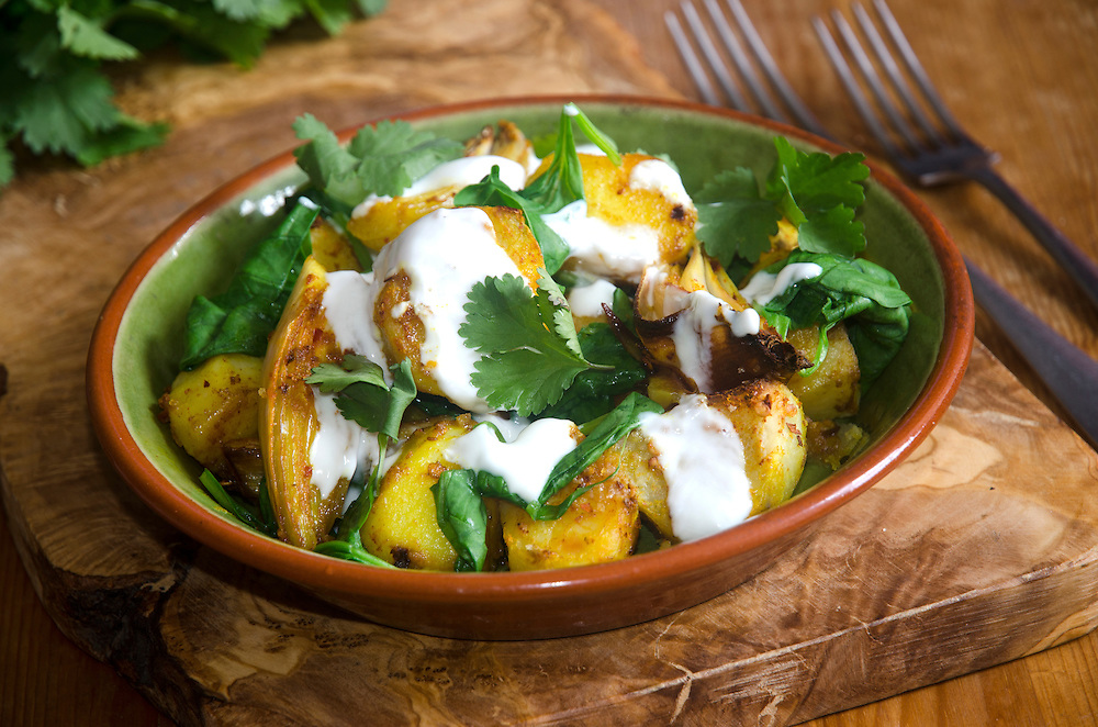 Potatoes with spices and spinach topped with yogurt