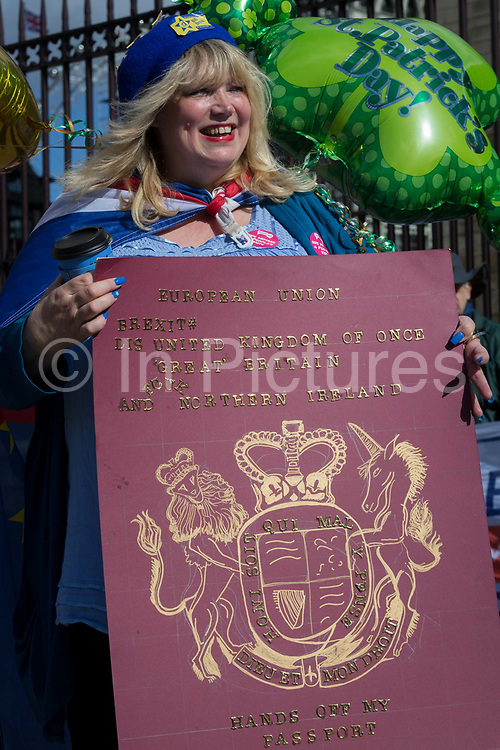 A woman protestor holds an altered British passport parody during a pro-EU brexit protest opposite Parliament, on 11th March 2019, in Westminster, London, England.