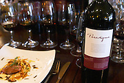 Slices of roast duck's breast placed on top of a ravioli with angle hair thin French fried potatoes on a white plate with a branch of thyme. And eight glasses of a vertical tasting of Angel A Mendoza Malbec Cabernet Sauvignon Pura Sangre Domaine St Diego Lunlunta Maipu Mendoza and a bottle of Paradigma, the private wine of Santiago Zemma of Zemma & Ruiz Moreno, The O'Farrell Restaurant, Acassuso, Buenos Aires Argentina, South America
