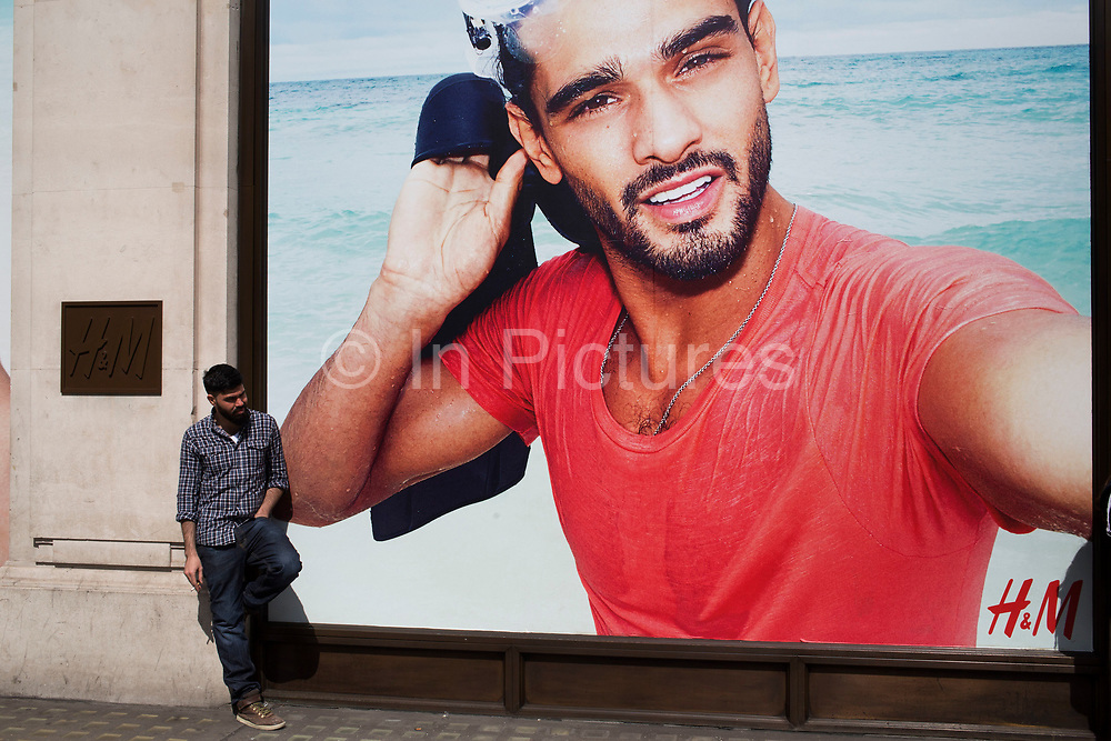 Young man with a beard standing outside a large scale advertising poster for fashion retail outlet H&M in London, United Kingdom. The man, having a cigarette break seems to be emulating the bearded model in the picture.