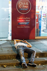 © Licensed to London News Pictures . 15/06/2014 . Manchester , UK . A man lies collapsed on the pavement below a Tesco Click and Collect banner . People on a night out in Manchester City Centre overnight , following England's defeat to Italy in the World Cup . Photo credit : Joel Goodman/LNP